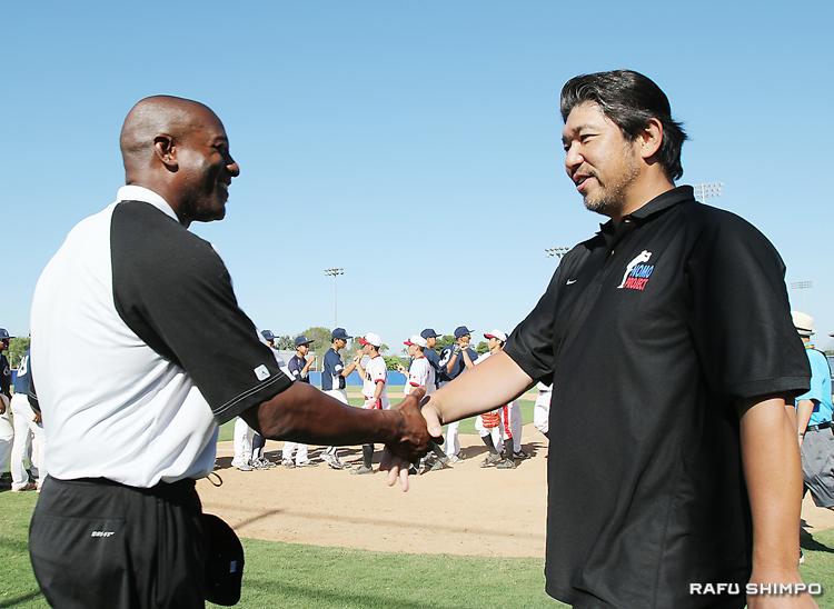 大会を終え、UYAチームのコーチ(左)と笑顔で握手を交わす野茂さん