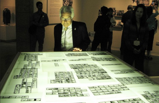 """Sus Ito looks at film strips made from his negatives, part of the """"Before They Were Heroes"""" exhibition at JANM.  (J.K. YAMAMOTO/Rafu Shimpo)"""