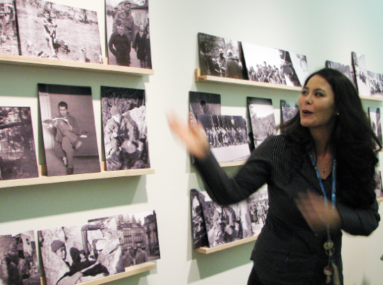 Curator Lily Anne Yumi Welty Tamai discusses Sus Ito's photographs of his buddies' daily lives in Italy, France and Germany.  (J.K. YAMAMOTO/Rafu Shimpo)