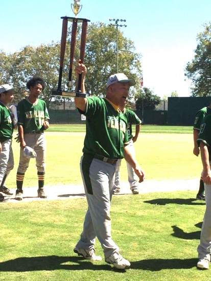 Manager/player Mike Furutani holds up the trophy.