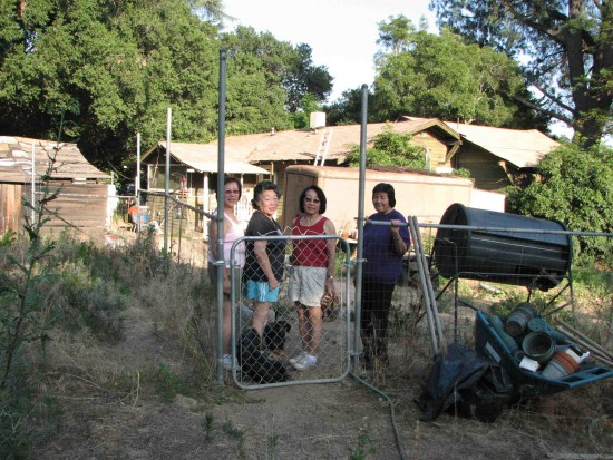 From left: Sisters Joyce Yuge, Cindy Yuge, Nadine Ishizu and Carolyn Yuge behind the family home while they were in the process of vacating the property. (J.K. YAMAMOTO/Rafu Shimpo)