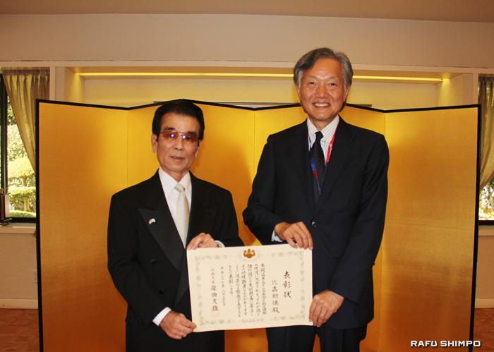堀之内総領事(右)から表彰状が手渡された比嘉氏