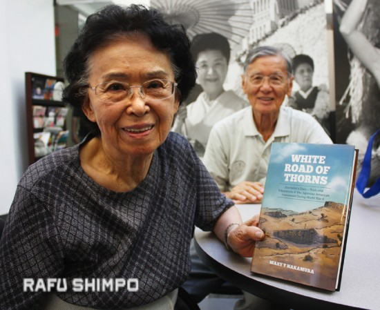 "Mary Y. Nakamura holds a copy of her book ""White Road of Thorns"" during a visit to **The Rafu Shimpo.** She is joined by her husband Edward. (MARIO G. REYES/Rafu Shimpo)"
