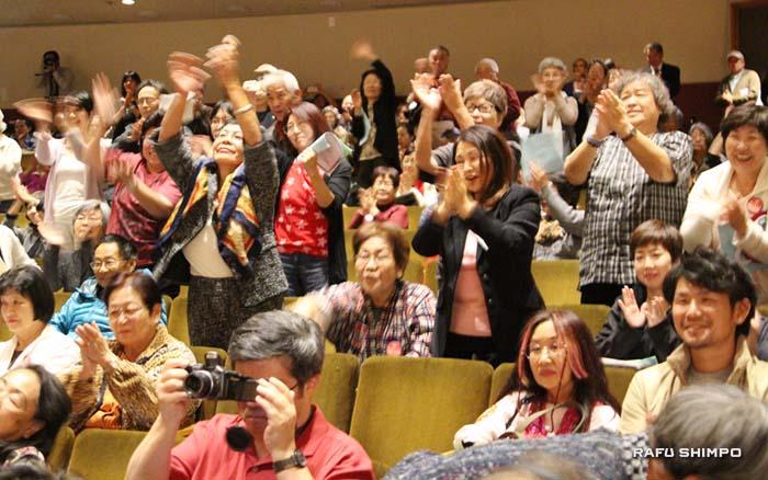 議員の「敬老を守る会」をサポートするスピーチ内容に立ち上がって拍手を送る参会者ら