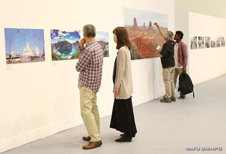 メンバーが世界各所で撮影した作品を鑑賞する来場者