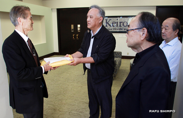 「守る会」の入江健二氏(左端)から、これまでに集まった5412人分の署名を受け取る「敬老シニアヘルスケア」人事部のジーン金森氏。その右手前がチャールズ井川「守る会」代表、右奥が大石剛司引退者ホーム施設長(写真=マリオ・レイエス)