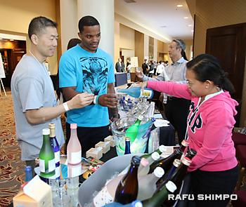 日本酒を試飲するジェイ・キムさん(左)とジョシュア・ロビンソンさん(右隣)
