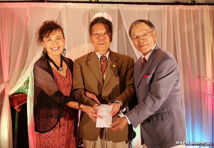 南加日系商工会議所の青木義男会頭(中央)に寄付金を贈呈する新原さん(左)と西さん(右)