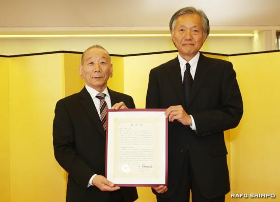 堀之内総領事(右)から表彰状を授与される豊島さん