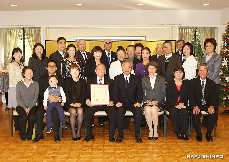 表彰式に参列した家族や親友とともに記念撮影に納まる豊島さん(前列左から4人目)