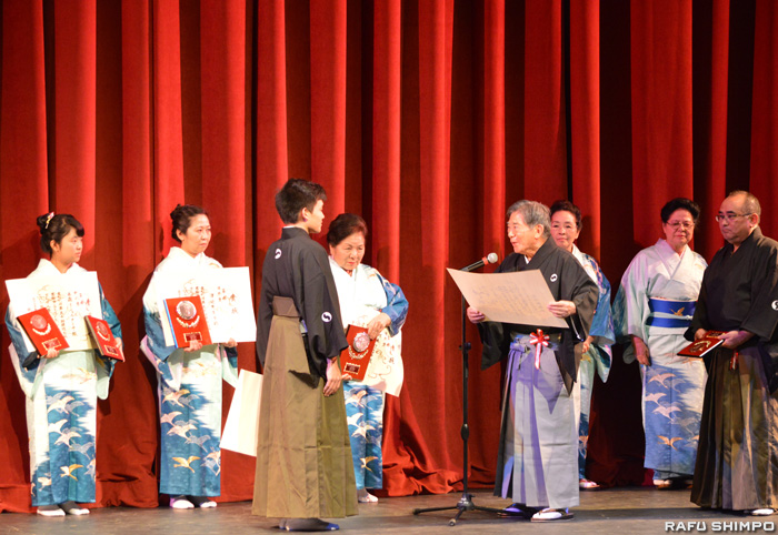 人間国宝・照喜名朝一顧問から表彰状を受けるプレホダ富男さん(前左)