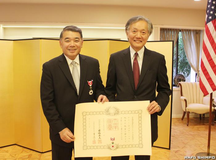 堀之内総領事(右)から勲章と賞状を伝達されたハラ氏