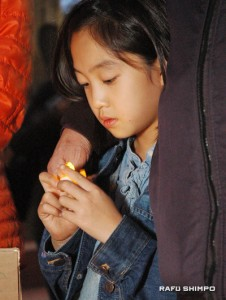 Naiya Kim holds a candle during the vigil. (MIKEY HIRANO CULROSS/Rafu Shimpo)