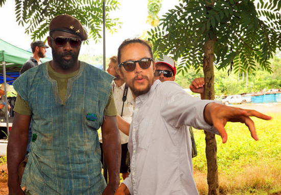 "Director Cary Fukunaga and actor/producer Idris Elba on the set of ""Beasts of No Nation."""