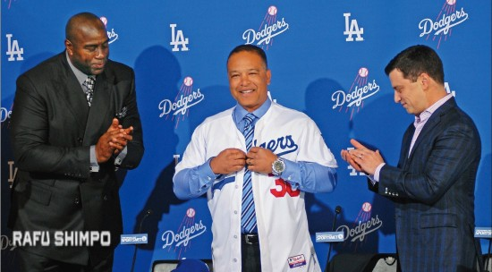Flanked by team co-owner Magic Johnson and president of baseball operations Andrew Friedman, Dave Roberts dons his jersey as he is introduced as the new manager of the Los Angeles Dodgers. Roberts, 43, takes over a team that has won its division three straight years, but has each time disappointed fans in the postseason. (MIKEY HIRANO CULROSS/Rafu Shimpo)