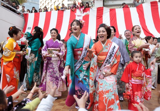 Miss Kimono and other members of L.A. Kimono Club toss mochi from the stage in Little Tokyo's Weller Court.