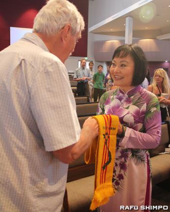 ベトナム戦争に出兵した元米兵(左)から和平の象徴としてスカーフを手渡されたフックさん