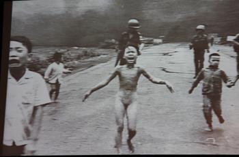 フックさんの講演会で映し出されたスライドの写真。当時9歳だった彼女は爆撃を受け、全身にやけどを負った。そしてウト氏が撮った「戦争の恐怖」と題したこの写真が後にピュリツァー賞を受賞。世紀の一枚として語り継がれている