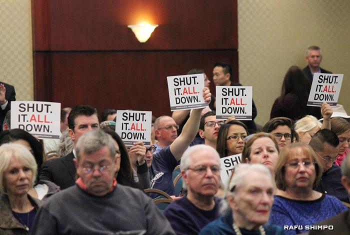 公聴会でガス貯蔵施設全体の閉鎖を求めるプラカードを掲げるポーターランチの住民たち(写真=吉田純子)