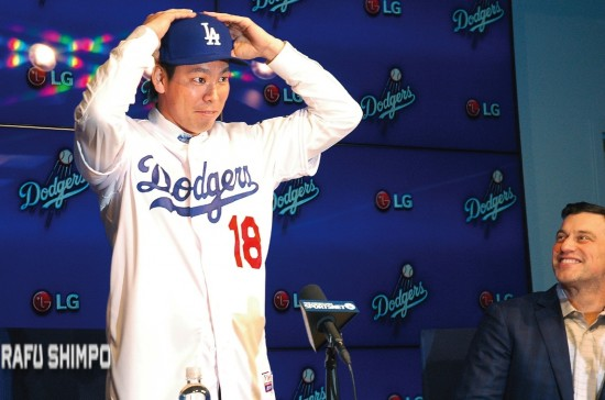 Kenta Maeda tries on his new cap during a press conference Thursday at Dodger Stadium, as Dodger President of Baseball Operations Andrew Friedman looks on.