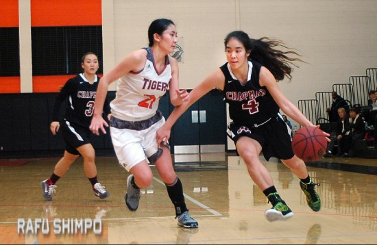 Chapman frosh Katelyn Serizawa drives past Occidental's Erin Matsumoto, during last Tuesday night's matchup at Oxy. At rear in Chapman's Lauren Sato. (MIKEY HIRANO CULROSS/Rafu Shimpo)