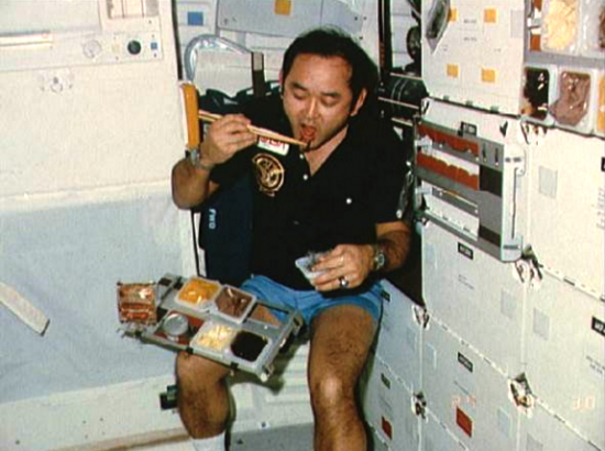 Ellison Onizuka eating with chopsticks during his first shuttle flight aboard the Discovery in 1985.