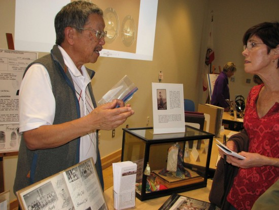 Library volunteer Richard Kawasaki discusses his family history. The doll in the glass case was made by his mother, Josephine Ashimoto, whose family farmed on the Palos Verdes Peninsula before World War II.