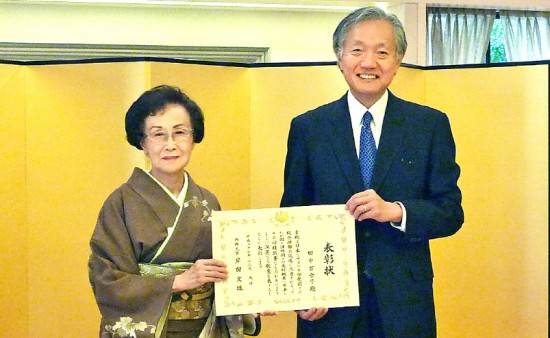 Soyu Yuriko Tanaka receives the Foreign Minister's Commendation in Honor of the 70th Anniversary of the End of the War from Consul General Harry Horinouchi on Dec. 9.