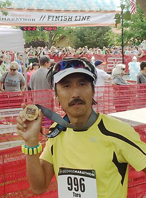 昨年のセントジョージ・マラソンで自己記録を更新し、完走のメダルを披露する吉田さん