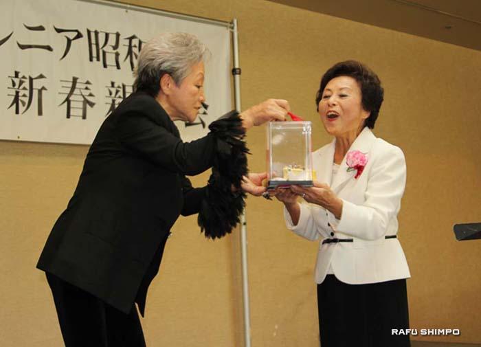 元会長の山口淑子さん(右)に得意の折り紙で新年にふさわしい「鶴と亀」を折ってプレゼントする新会長の川口利恵さん(左)。