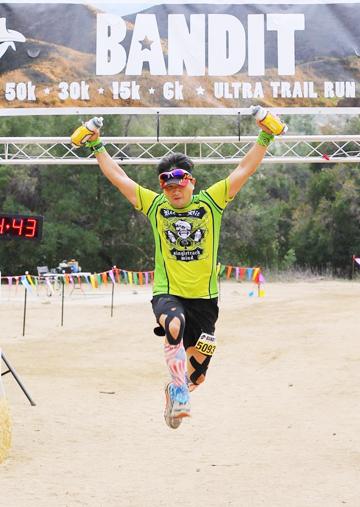 50キロのウルトラトレイルランに参加した鈴木さんは、両手を挙げ飛び上がってゴールし、喜びを表現