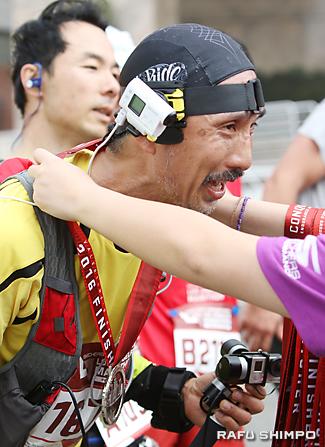 完走を果たしメダルを首に掛けられる吉田太郎さん。頭と手には、撮影に使った小型カメラが見られる
