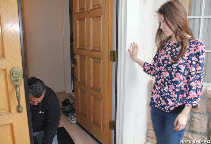 業者が自宅の玄関ドアにガス侵入を防ぐ作業を行う様子を見守る日比野さん=1月30日