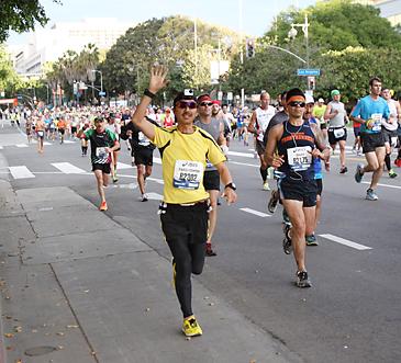 2014年のLAマラソンに参加し、小東京の1街で沿道の声援に応えて手を振って走る吉田さん。帽子には、小型カメラが取り付けられている