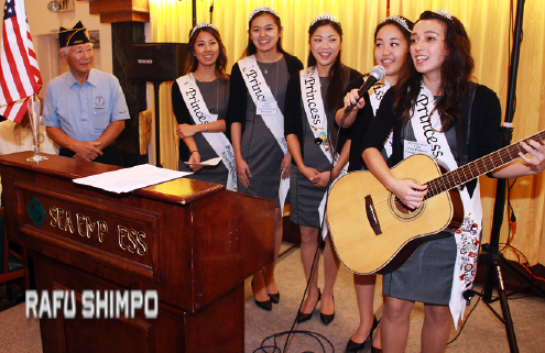 "Nisei Week First Princess Veronica Ota on guitar leads the crowd in ""God Bless America."" She is joined by Nisei Week Court members (from left) Michelle Hanabusa, Camryn Sugita, Tamara Teragawa and Karen Mizoguchi."