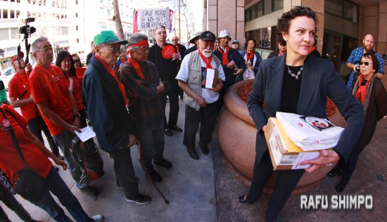 Tania Ibanez (foreground) meets demonstrators outside the Reagan Building in downtown Los Angeles, home of the Los Angeles office of the Attorney General. The protest was organized by Mo Nishida (center, wearing black cap), co-chair of the Ad Hoc Committee to Save Keiro. (MARIO G. REYES/Rafu Shimpo)