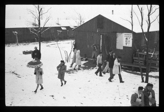 People leaving the Buddhist church in the Block 13 recreation hall at Manzanar in the winter of 1943. (Photo by Ansel Adams/Library of Congress)
