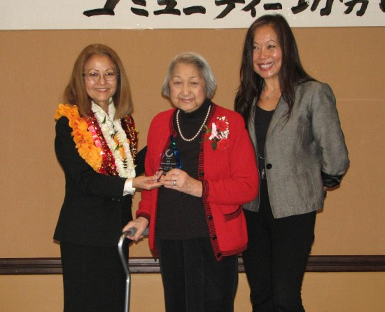 """JCCSC President Kitty Sankey presents the Nikkei Spirit Award to the late John """"JT"""" Tamaki, represented by his mother Anna Mae and his sister Mary."""