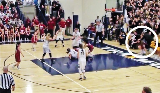 A screen grab from Glen Kumamoto's video of the Feb. 25 CIF playoff game between McClatchy High (dark uniforms) and host Oak Ridge shows a scrum for the ball as well as a McClatchy player being momentarily prevented by an Oak Ridge student from re-entering the court (circled at far right.) The game was marred by racially-charged taunts and insensitive remarks about body and appearance, directed at McClatchy players and cheerleaders from the Oak Ridge student cheering section.
