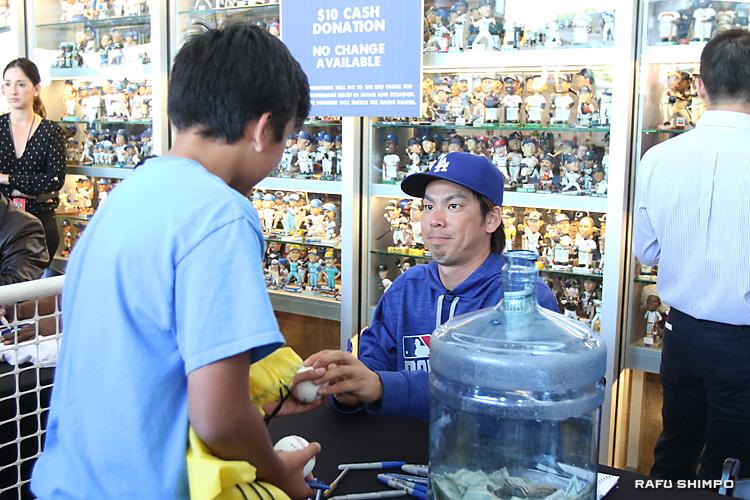 サインしたボールをファンの少年に手渡す前田投手(右)