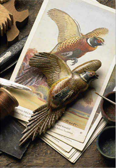 While imprisoned at Poston, Ariz., Sadao Oka, a farmer from Salinas, joined a bird-carving group and learned to sketch a bird outline on flat wood, carve and sand it into a three-dimensional form, then paint it with realistic colors. Oka made more than two dozen bird pins in camp, taking special care to define every feather and detail. (Photo by Terry Heffernan/Heffernan Films)