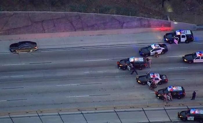 3時間におよぶカーチェイスの末、警察に取り囲まれた犯人の車(黒色の車)