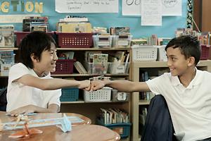 クラスメートに鶴の折り方を教え、友情を深めるさとし(右)