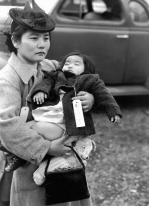 With her daughter in her arms, Fumiko Hayashida waits to board a ferry from Bainbridge Island on March 30, 1942. They were sent to Manzanar. (Museum of History and Industry)