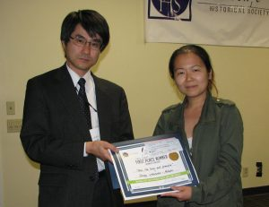 Shirley Watanabe-Nishida receives her prize from Deputy Consul General Izuru Shimmura.