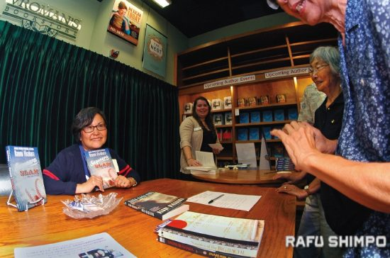 "Naomi Hirahara poses for a photo with her latest work in the Mas Arai mystery series, ""Sayonara Slam,"" during an author reading and discussion at Vroman's Bookstore in Pasadena on May 2. (MIKEY HIRANO CULROSS/Rafu Shimpo)"