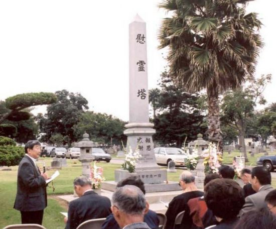 Kenji Koda speaks in front of the ireito during Memorial Day ceremonies at Woodlawn Cemetery in 2002. (VJCC)