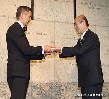 全米日系人博物館のグレッグ・キムラ館長(左)に禎子さんの折り鶴を手渡す佐々木雅弘さん