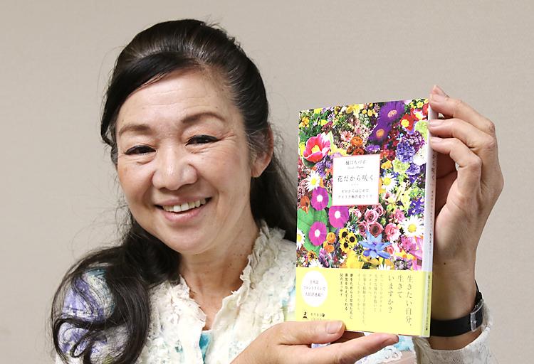 著書「花だから咲く」を披露する樋口さん。若い日本人女性たちに「夢を追い求めて」と語りかけ、勇気を与える