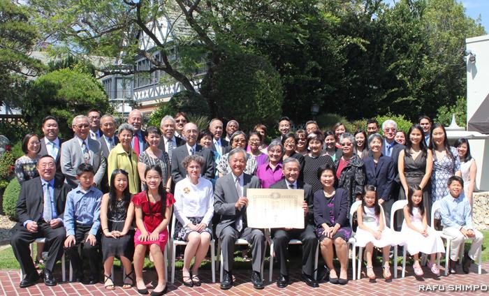 親族や友人など伝達式の出席者と記念撮影に納まるニシオ氏(前列右から5人目)